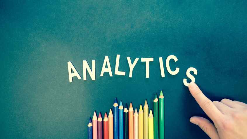 An image of the word analytics on a chalkboard with colored pencils underneath.